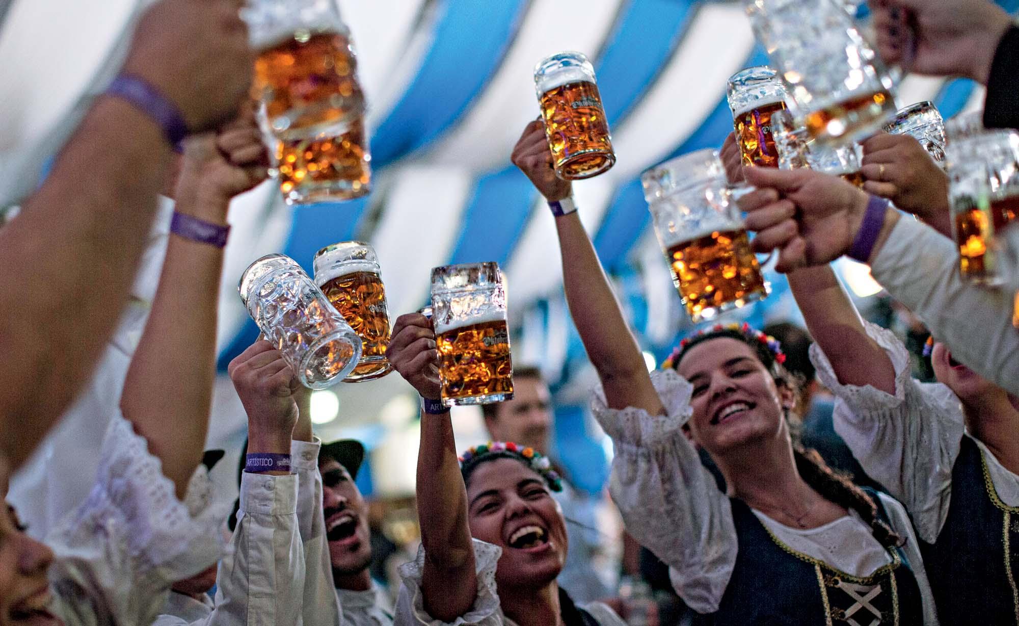 Um grupo de pessoas levanta caneca de cervejas em uma tendz