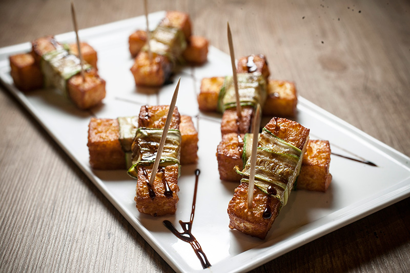 Gajos: palitos de queijo de coalho fritos, enrolados em fatias de abobrinha grelhada e finalizados por redução de vinagre balsâmico