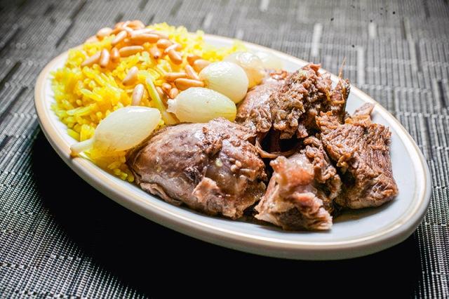 Carneiro ao forno com arroz de açafrão coberto por pinhole mais cebolas pequenas