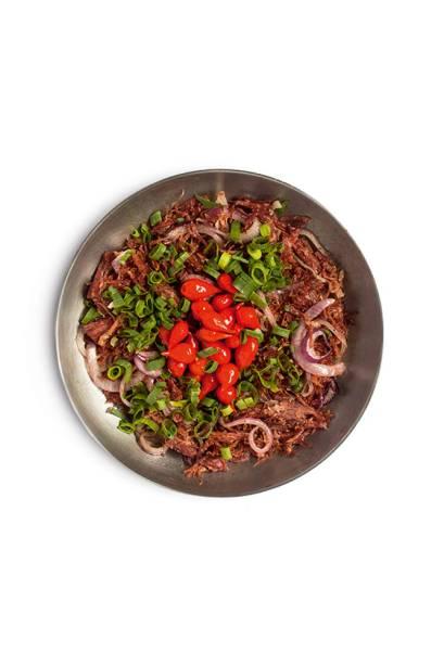 A carne-seca, desfiadinha, leva cebola-roxa
