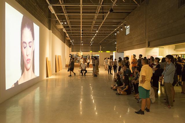 Público assiste um dos vídeos da exposição na noite de abertura do galpão