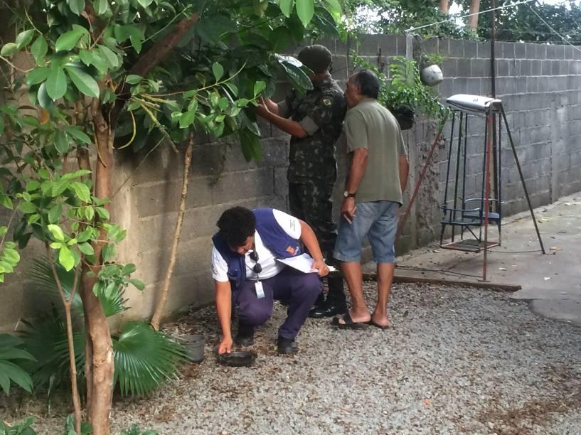Funcionária retira vaso de planta com água parada na casa de morador do Limão