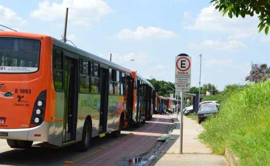 Ao lado do ponto de ônibus, ciclofaixa da Avenida Escola Politécnica, com pintura apagada e poça