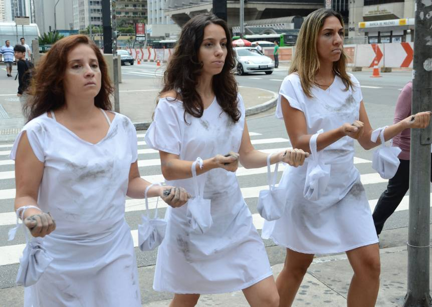 """Três atrizes de um grupo de teatro """"Pedra Rubra"""" homenageiam o Dia Internacional da Mulher com uma performance teatral, representando as mulheres que morreram incendiadas em 1857 em uma fábrica de tecidos, nos Estados Unidos, ao lutar por seus direitos"""
