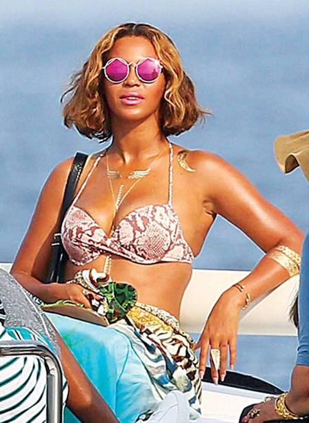 A cantora Beyoncé usa colares, braceletes e desenhos variados durante suas férias