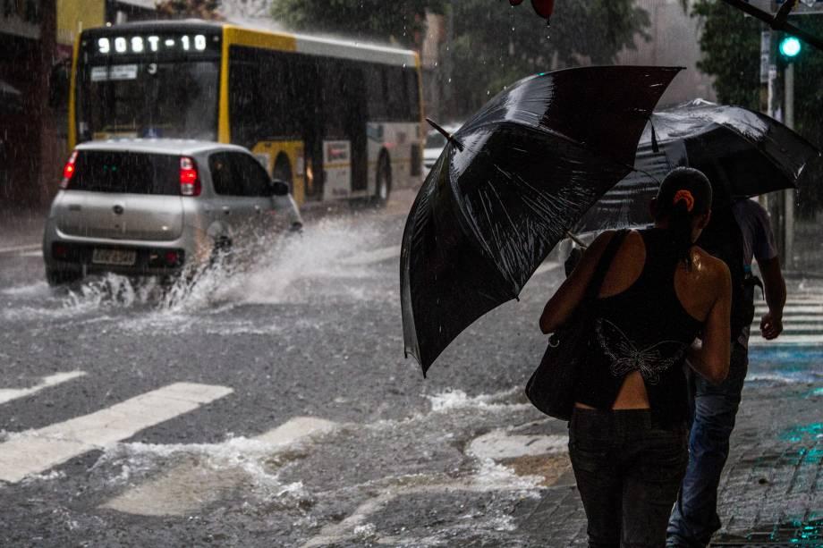 Pedestres se protegem da chuva na Rua Augusta, na região central, nesta quarta-feira (25)