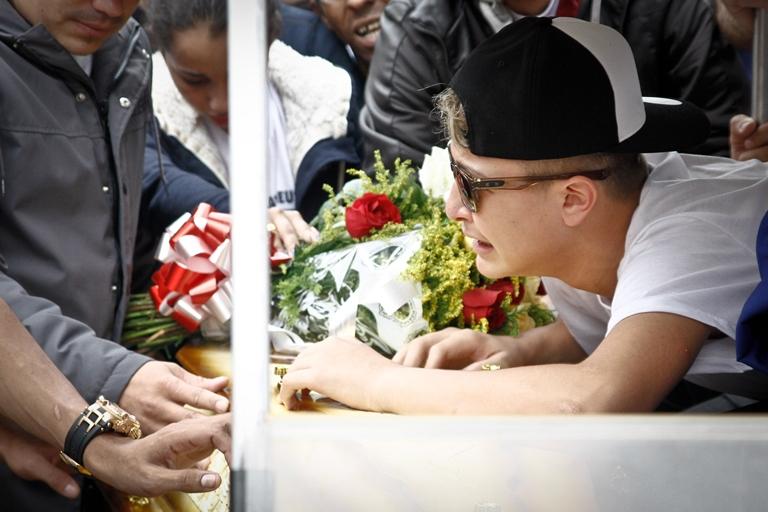 MC Gui chora sobre o caixão de seu irmão, enterrado no Cemitério da Vila Alpina, Zona Leste