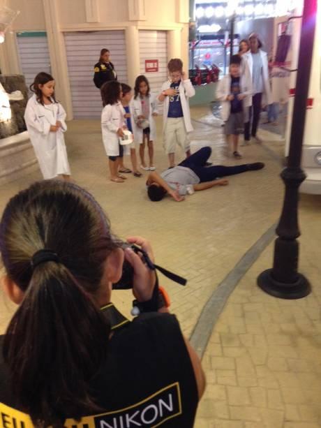 Enquanto algumas crianças protagonizam um atendimento medico, outras fazem o papel de fotógrafo