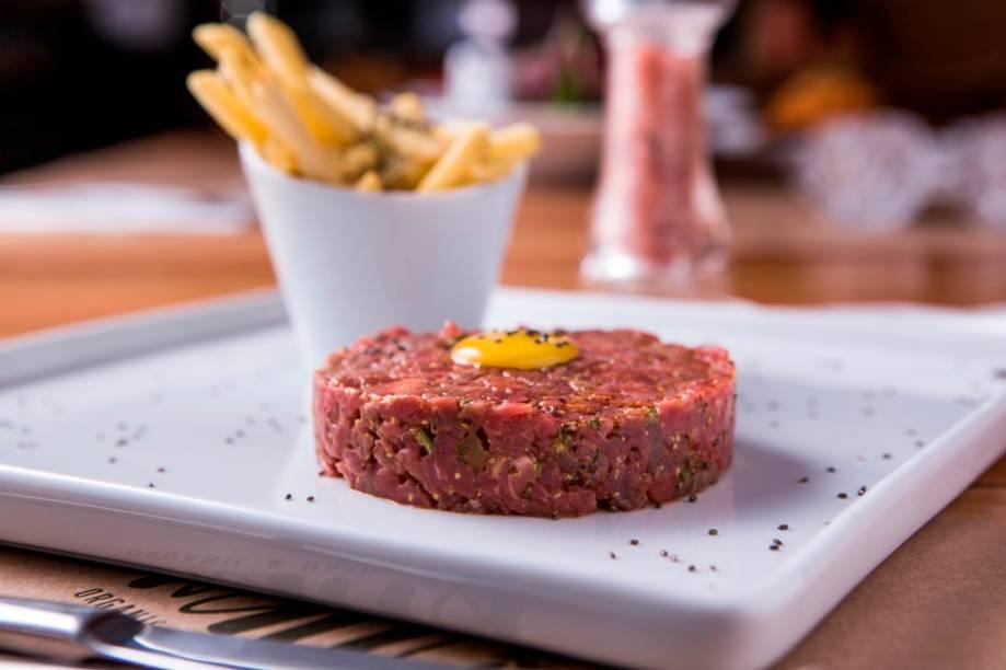 Coberto por uma gema ovo de codorna, o steak tartare chega junto de batata frita ao alecrim