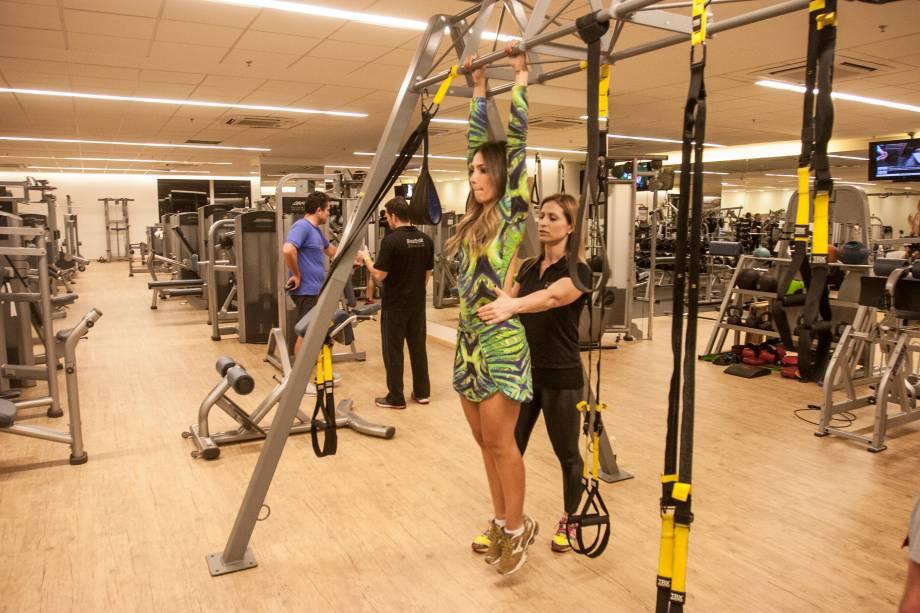 Pendurada na barra: faça a flexão do quadril através da elevação dos joelhos (aproximar coxas do abdômen). Quatro série de quinze repetições.