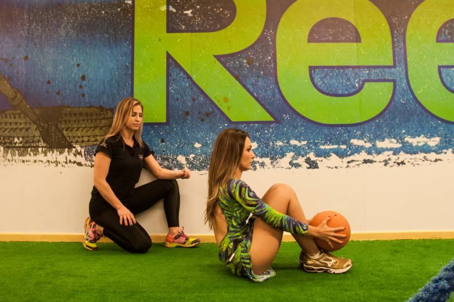 Abdominal com bola: faça um movimento de levantar e traga o peso acima dos pés. Quatro séries de vinte repetições.