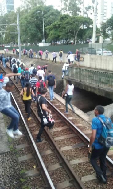 Pessoas andam nos trilhos do trem