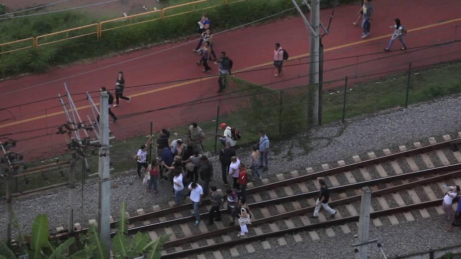 Passageiros caminham pela linha da CPTM próximo à estação Pinheiros após falha técnica em trem