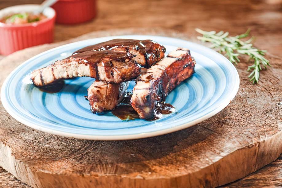 As macias costelinhas de porco chegam soltando do osso e besuntadas de molho barbecue