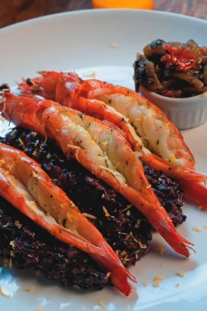 Trio de camarões sobre arroz negro
