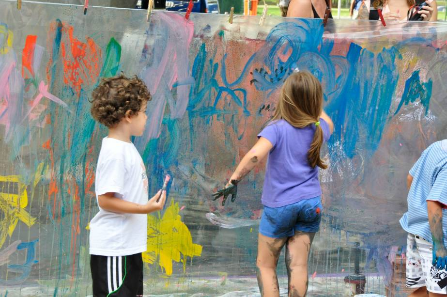 As criações das crianças são expostas em um varal, formando um grande painel