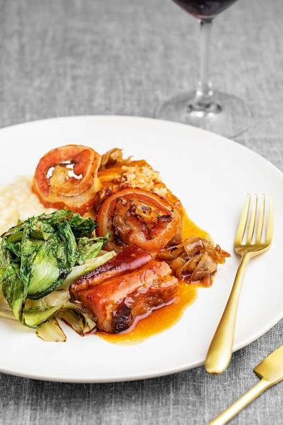 Barriga de porco em três versões: fresca e assada, curada e passada na grelha e defumada na forma de uma lâmina fina frita, como um bacon crocante, servida com risoto de parmesão, escarola tostada e cebola caramelizada
