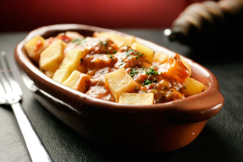 Porção de batatas-bravas com caldo de mariscos no molho de tomate