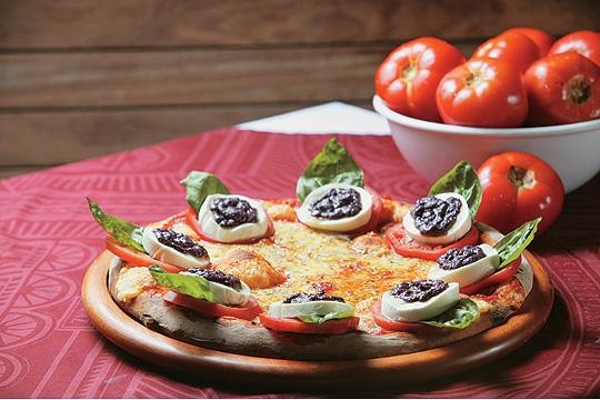 Caprese: cobertura de mussarela e fatias de tomate coroadas por uma composição de mussarela de búfala, folhas de manjericão gigante e pesto de azeitona preta