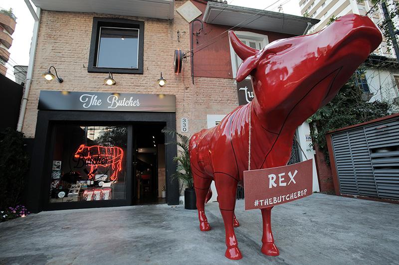 O reluzente touro vermelho Rex fica na entrada da loja