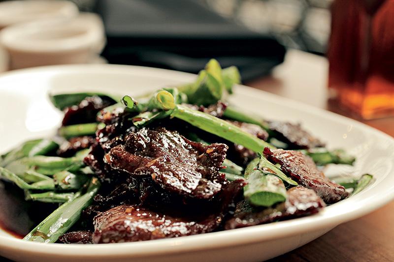 Mongolian beef traz fatias de carne na chapa carameladas no molho de shoyu e alho com cebolinha verde