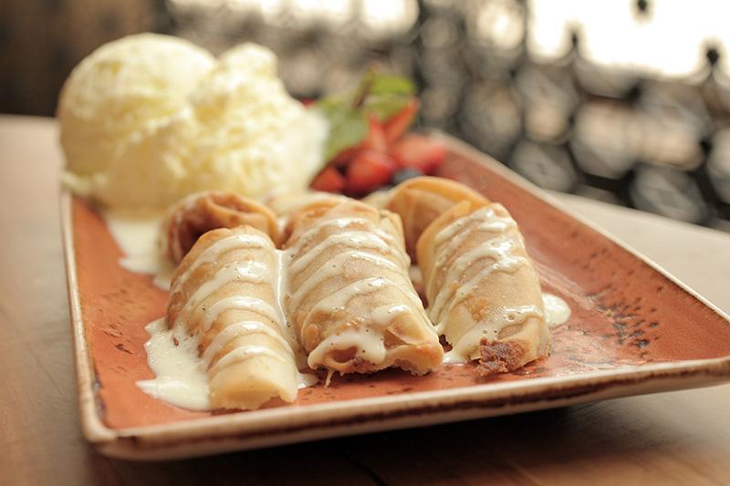 A banana caramelada é coberta por caldas de caramelo e de baunilha, servida com sorvete de abacaxi e coco