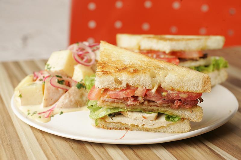 Club sandwich com peito de frango e bacon com salada e batata