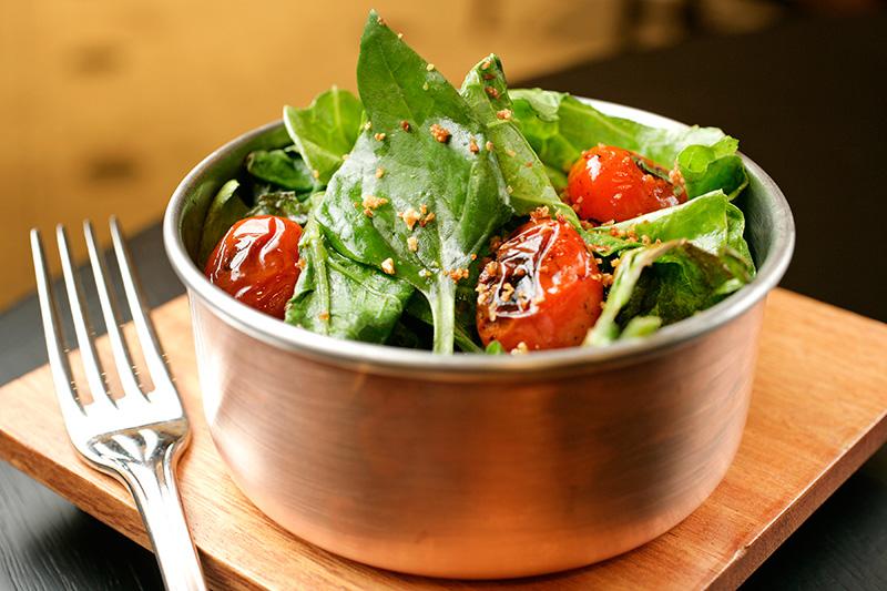 Panelinha de couve e espinafre salteado com tomatinhos e alho