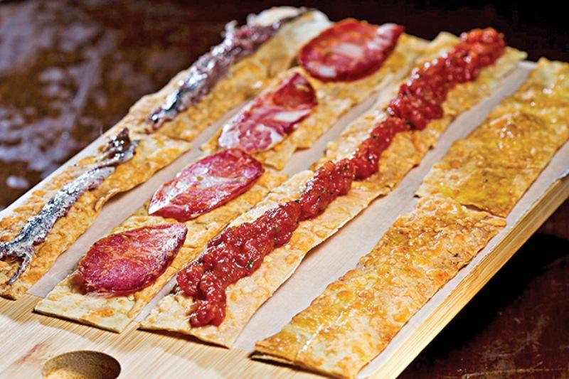 Terra, amore e fantasia: um quarteto de crostini fino com aliche, calabresa seca, tartare de tomate e azeite da Puglia