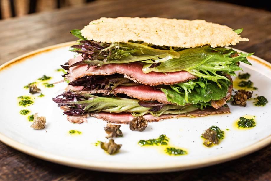 Salada de folhas intercaladas por rosbife e uma tela de pão crocante