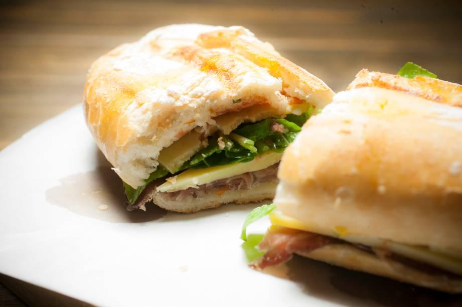 No pão semi-italiano, o sanduíche de copa curada, queijo campo redondo, rúcula e molho de tomate