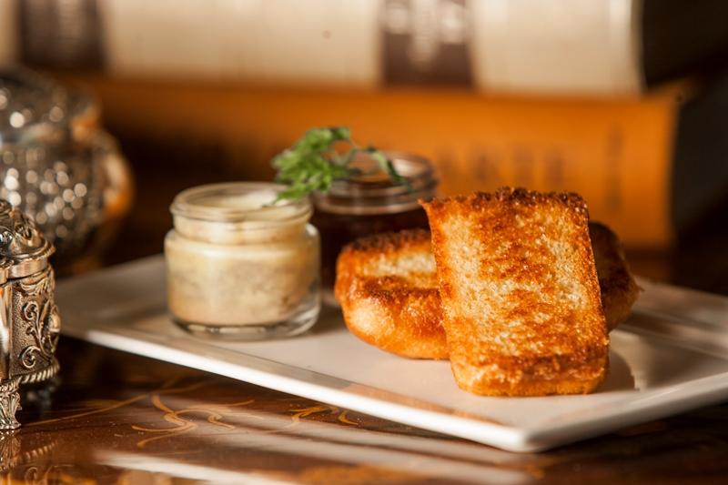 A terrine de foie gras com geleia de frutas vermelhas chega junto de um brioche dourado