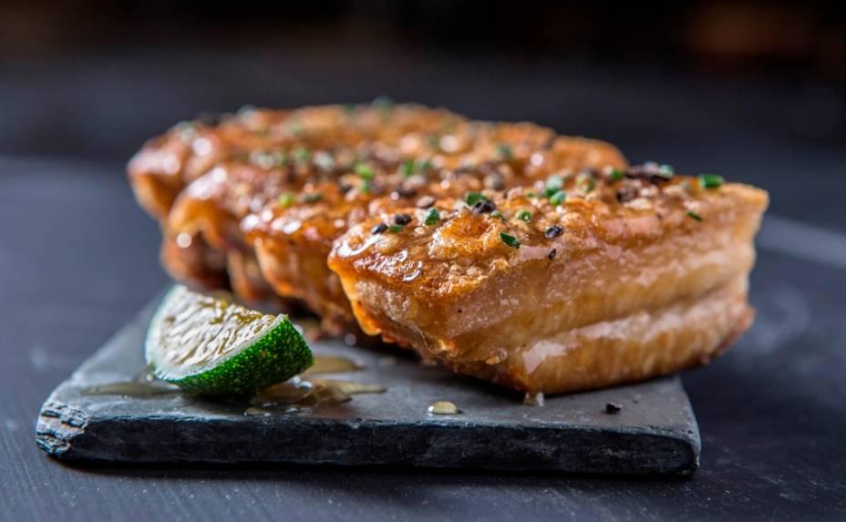 A ótima barriga de porco de pele crocante é temperada com pimenta-do-reino e mel
