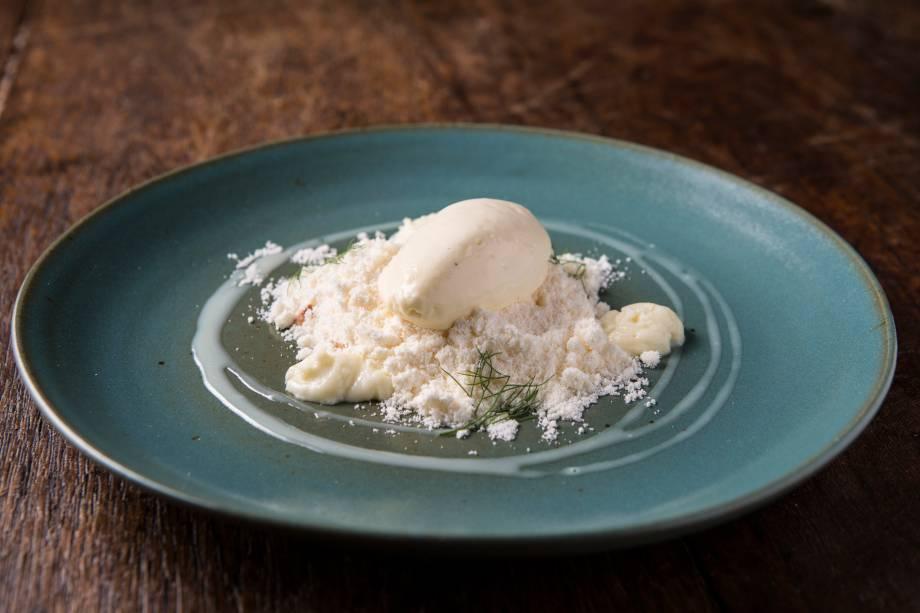 Sobremesa de areia de baunilha sobre um maracujá, castanha-de-caju e sorvete de chocolate branco