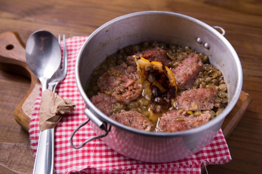 Em uma marmita, o embutido cotechino vem em um cozido de lentilha