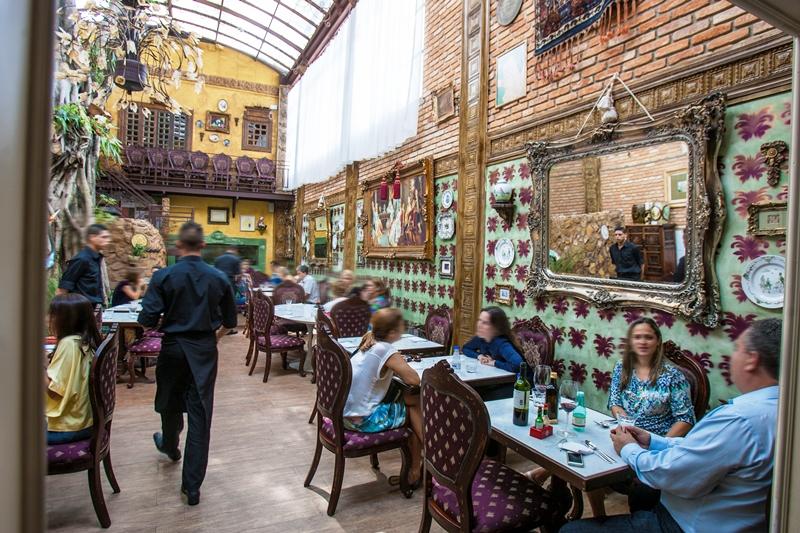 O ambiente tem decoração divertida , que vai de papel de parede a tijolos aparentes, além de espelhos com molduras douradas