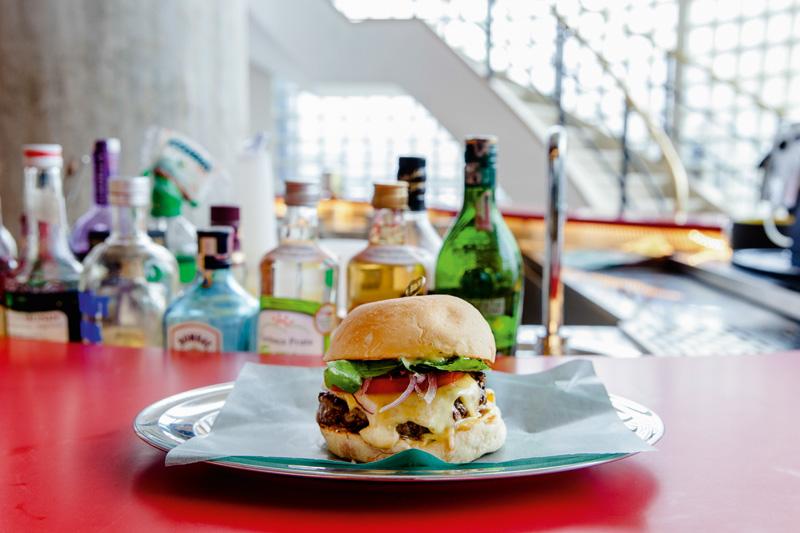 O sanduíche que recebe o nome da casa tem 150 gramas de carne entre as fatias de pão e leva ainda queijo gruyère, cebola-roxa, tomate e folhas de rúcula.