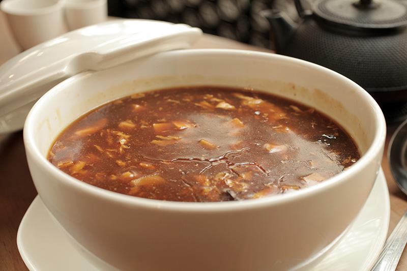 A hot and sour soup, levemente picante, combina tofu, brotos de bambu, cogumelos e ovos em caldo de frango