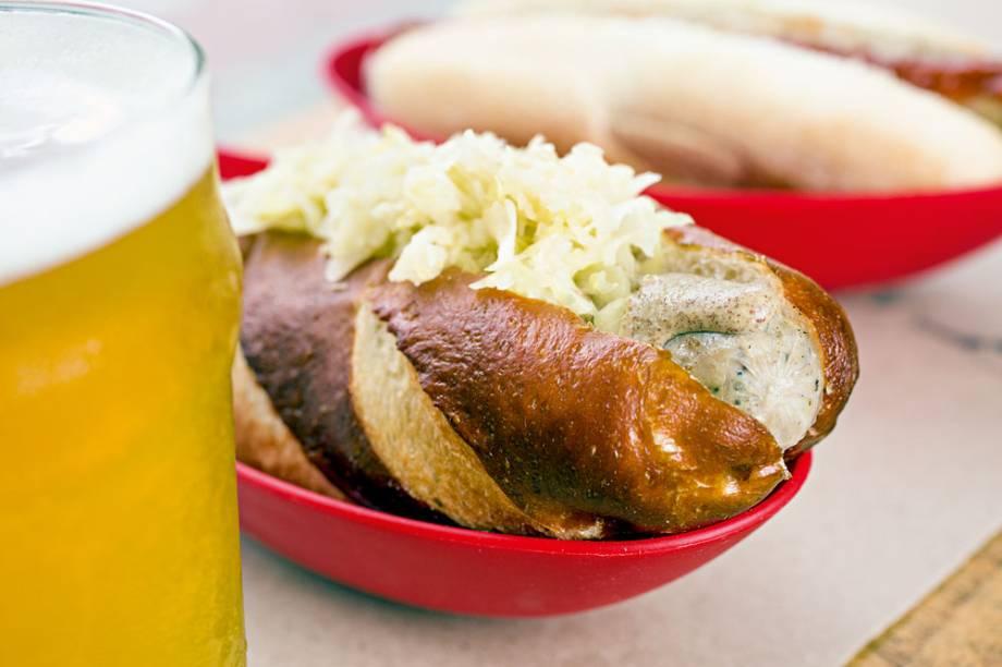 Cachorro-quente com salsicha bratwurst, mostarda escura e chucrute: pão de massa de pretzel