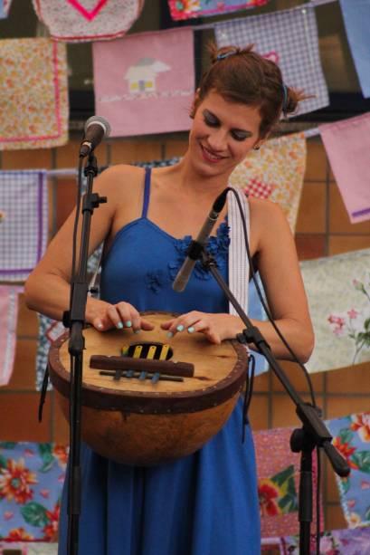 Cris Bosch com o instrumento de percussão ngongoma, com som semelhante ao da kalimba