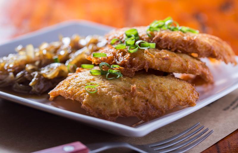 kartoffelpuffer: três panquequinhas do batata ralada crocantes com cebola caramelada