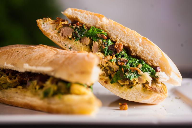 Sanduíche de pernil com geleia de bacon e folhas de mostarda na ciabatta