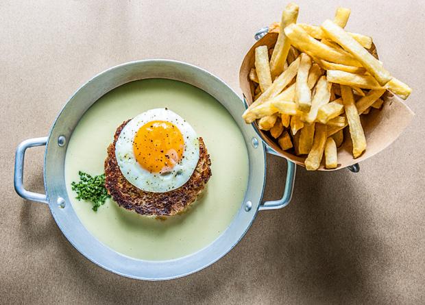 Hambúrguer de alheira com ovo sobre queijo da Serra da Estrela e fritas