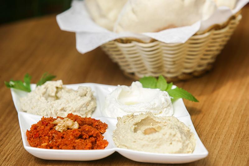 No quarteto de pastas vão muhamara (pasta de pimentão vermelho), babaganuche (berinjela), coalhada seca e homus (grão-de-bico)