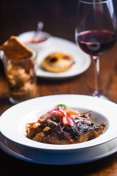 Cordeiro assado no forno a lenha acompanhado de feijão-branco, batata, cenoura e uma refrescante salada de tomate e cebola-roxa crua por cima