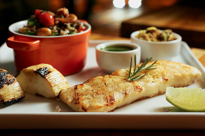 Pirarucu servido na companhia de palmito pupunha grelhado, molho de rúcula e arroz de espinafre com castanha-de-caju e tomatinhos