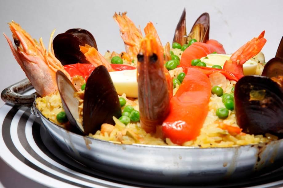 Paella valenciana : elaborada com arroz , açafrão, frango, legumes, bacon e frutos do mar