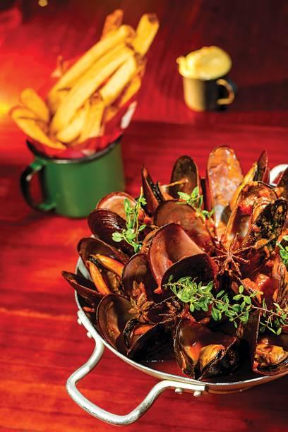 Moules frites à l´indienne: mariscos cozidos no molho de tomate ao curry amarelo, cardamomo e anis