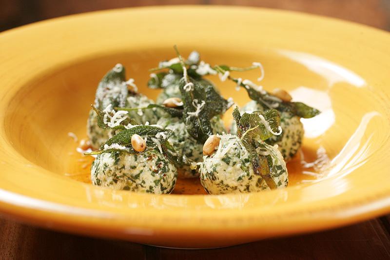Nhoque de ricota e espinafre ao molho de manteiga, pinhole e sálvia frita
