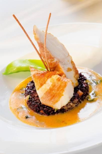 Peixe tamboril: envolto em presunto cru com emulsão de sálvia e arroz negro